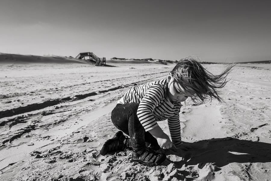 little girl playing on the beach alone in the wind