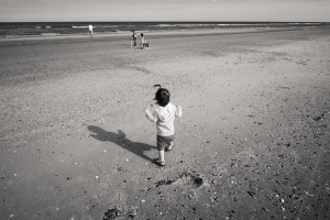 Baby walking to catch up with dad, brother, and sister on beach