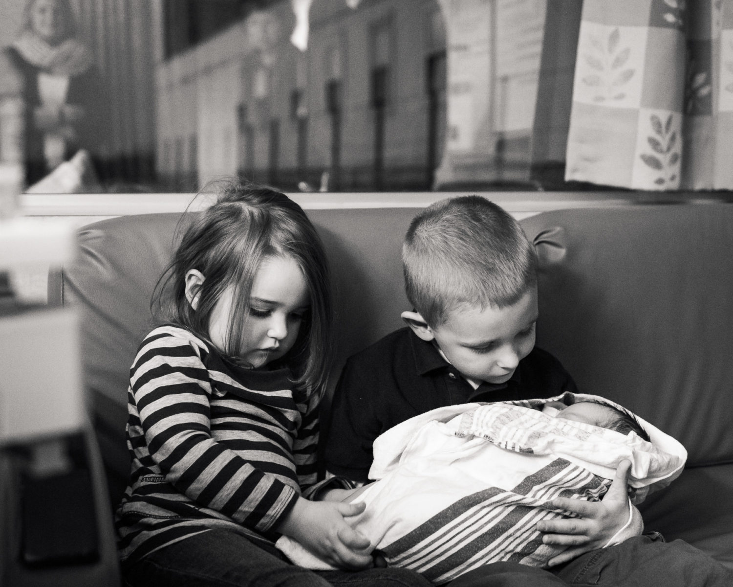 Big Brother and Big Sister holding newborn baby girl