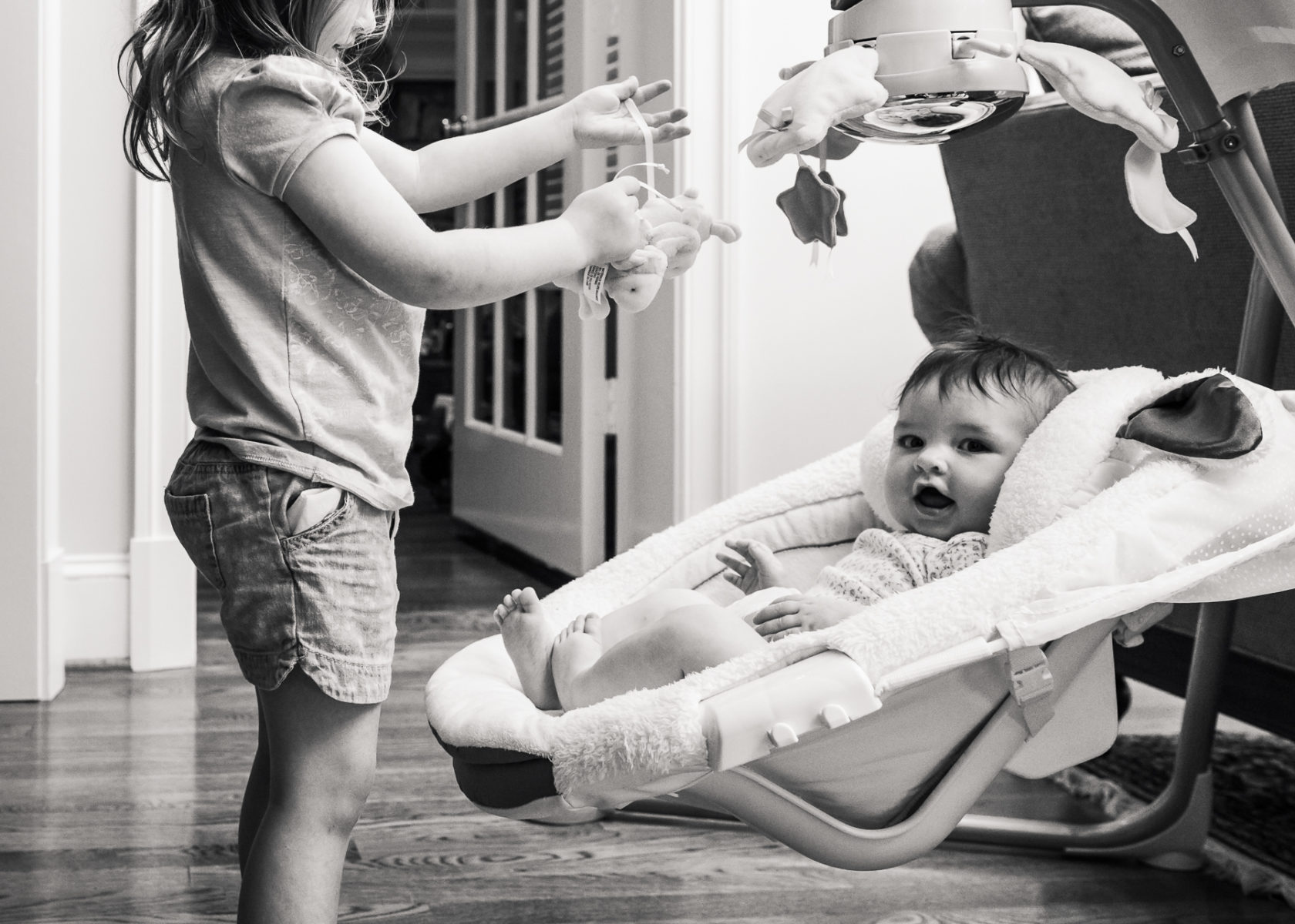 Baby in infant swing watches big sister take toys