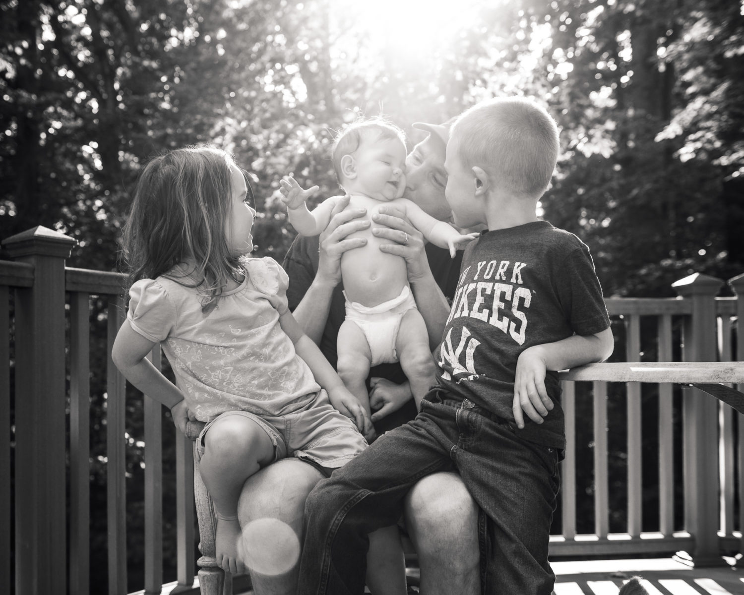 dad holding toddler, son, and daughter on deck - beautiful light