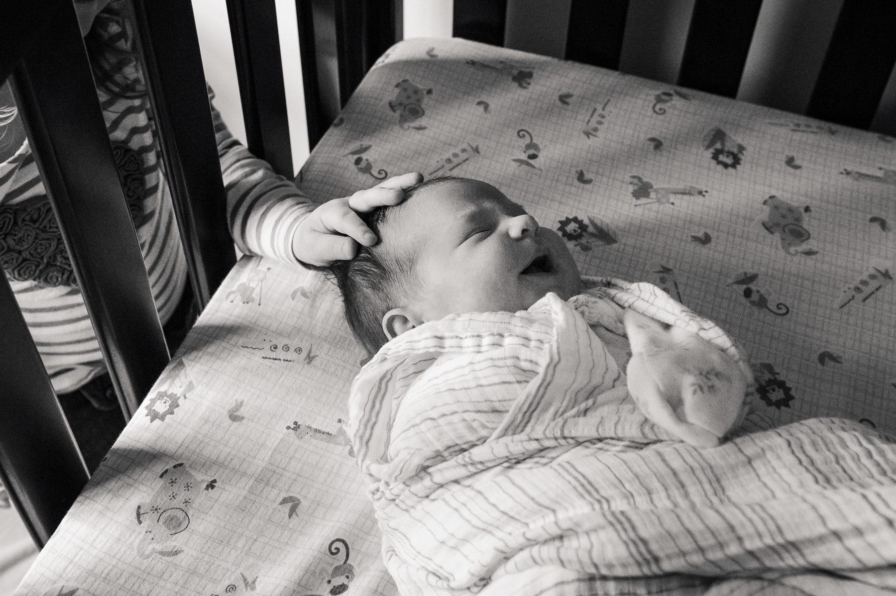 Big sister touching newborn sister's head through the crib