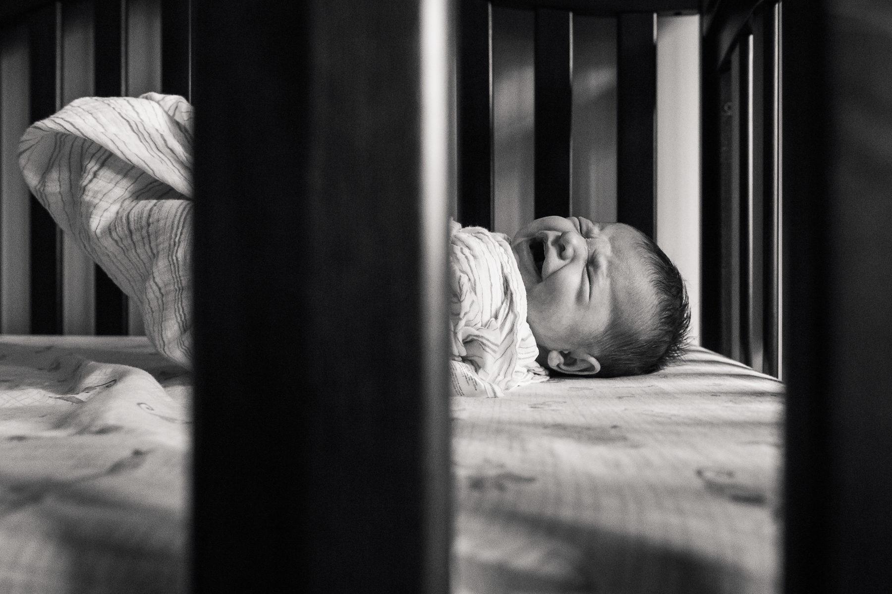 Newborn baby girl crying in crib