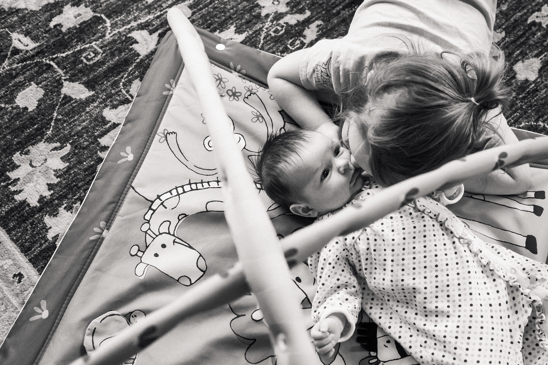 Big sister kissing newborn baby sister in her baby gym