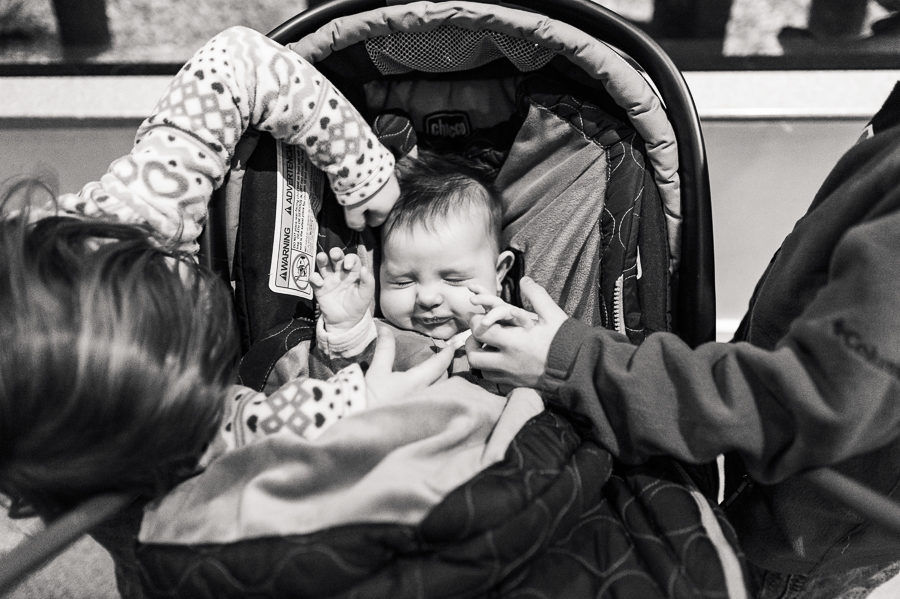 Big brother and big sister touching sleeping baby in car seat