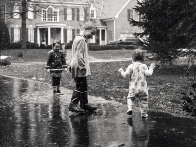 baby walking through rain to puddle in driveway with big brother and sister