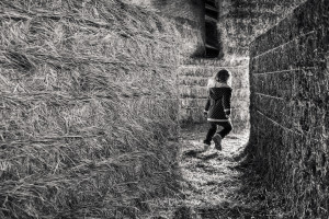 girl running through hay maze