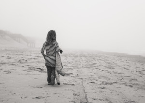 Girl walking on beach in the mist at the Outer Banks