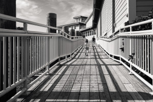 brother and sister running up boardwalk with shadows