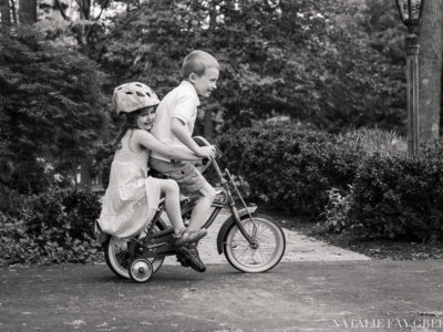 Little sister riding on the back of big brother's bicycle