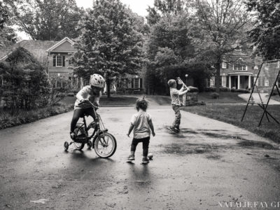 children playing in the driveway after rain | lacrosse | riding a bicycle with training wheels