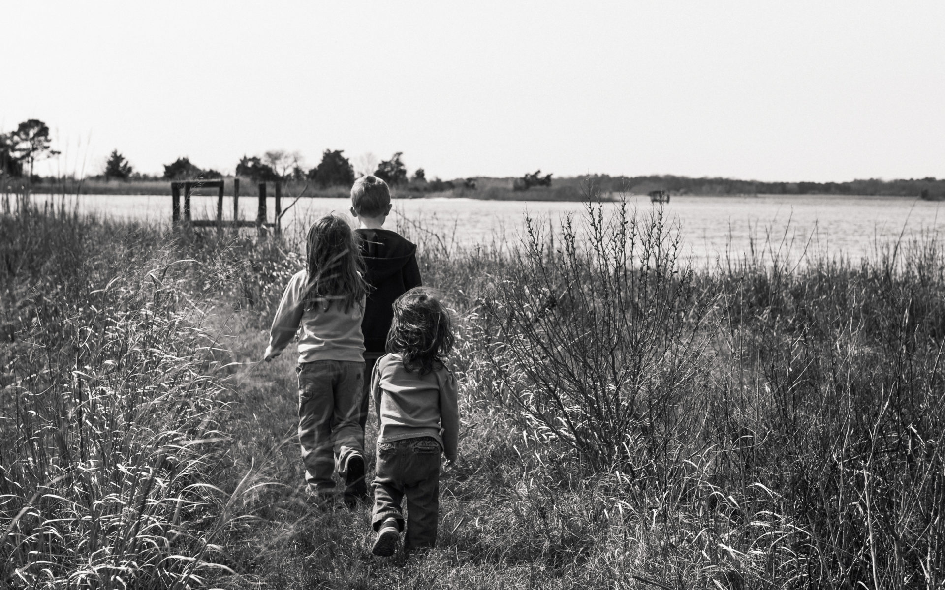brother and younger sisters walking through march on Eastern Shore