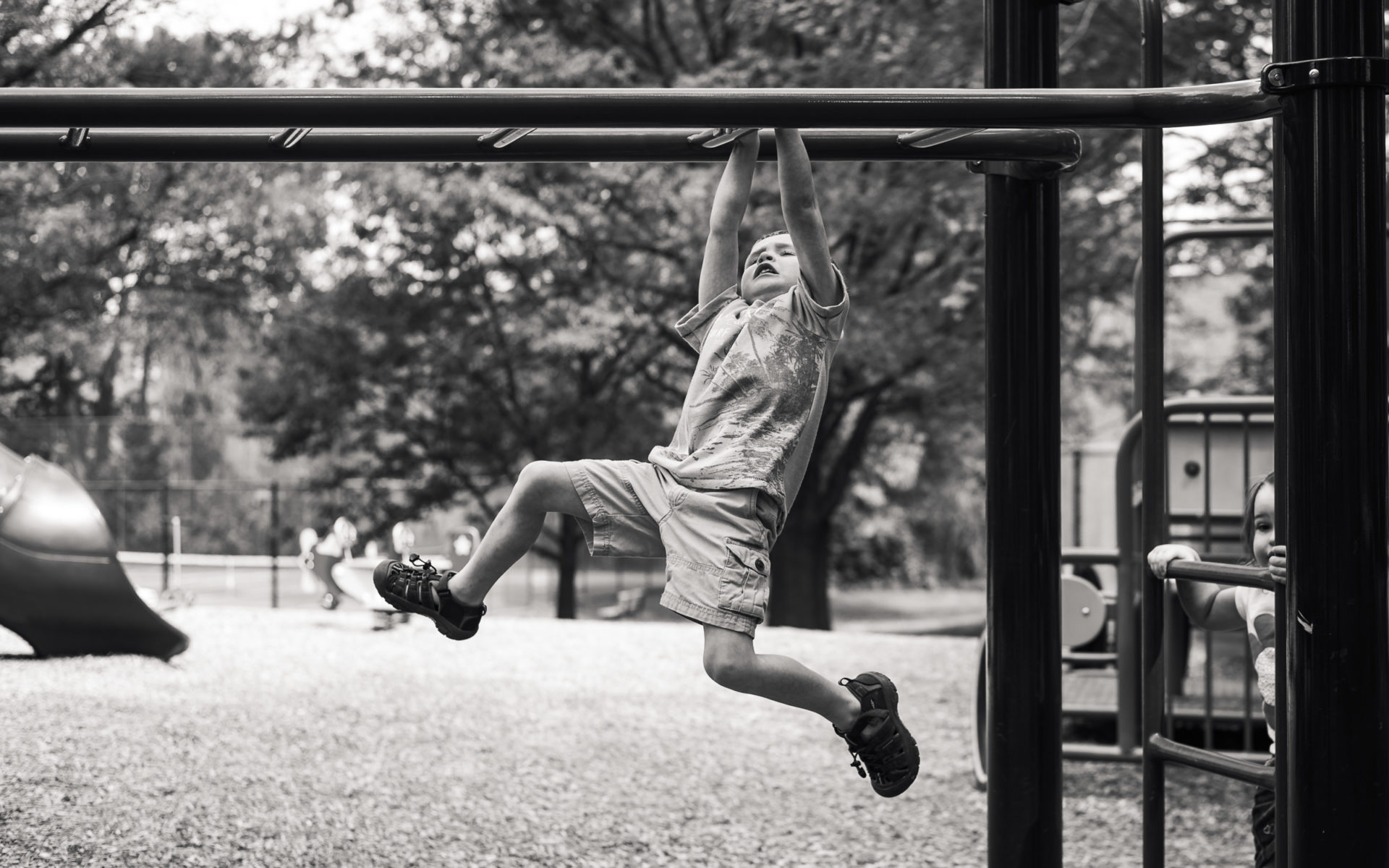 boy crossing the monkey bars for the first time