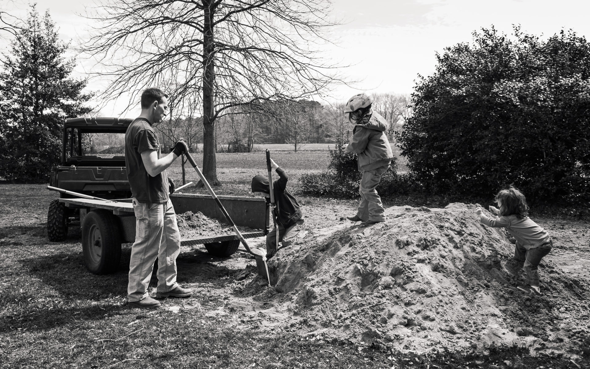 children and dad moving large pile of dirt