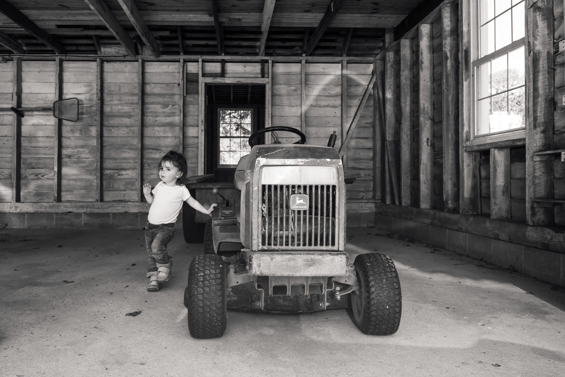 toddler leaning on John Deere tractor