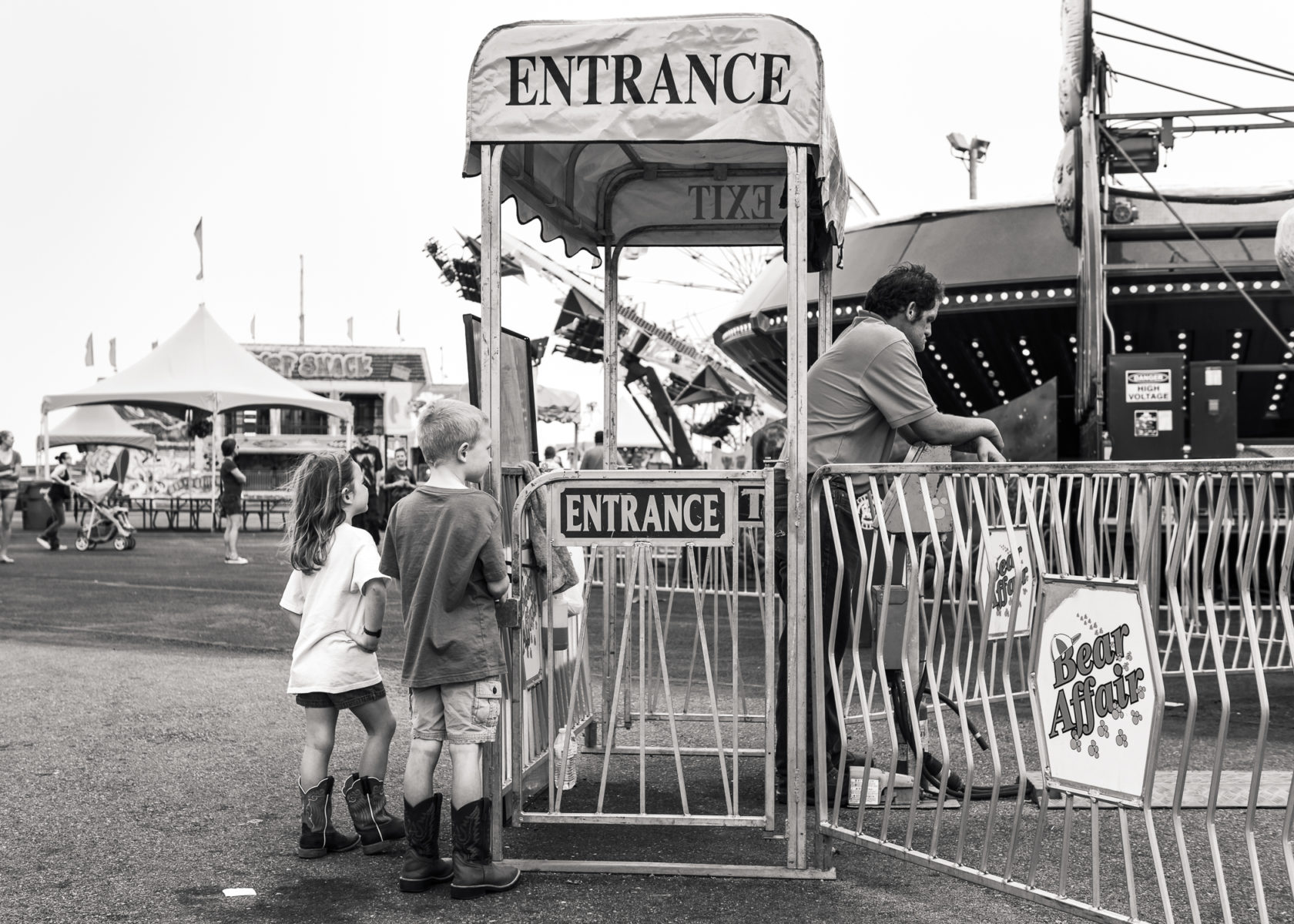 children and carnival worker waiting for the next midway ride