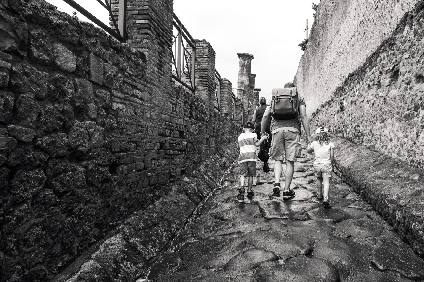children and dad walking into Pompeii