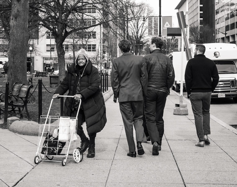 Homeless woman in Washington DC walks past business millennials