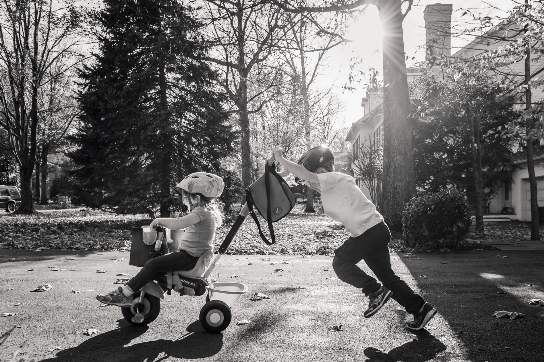 brother pushing sister on tricycle