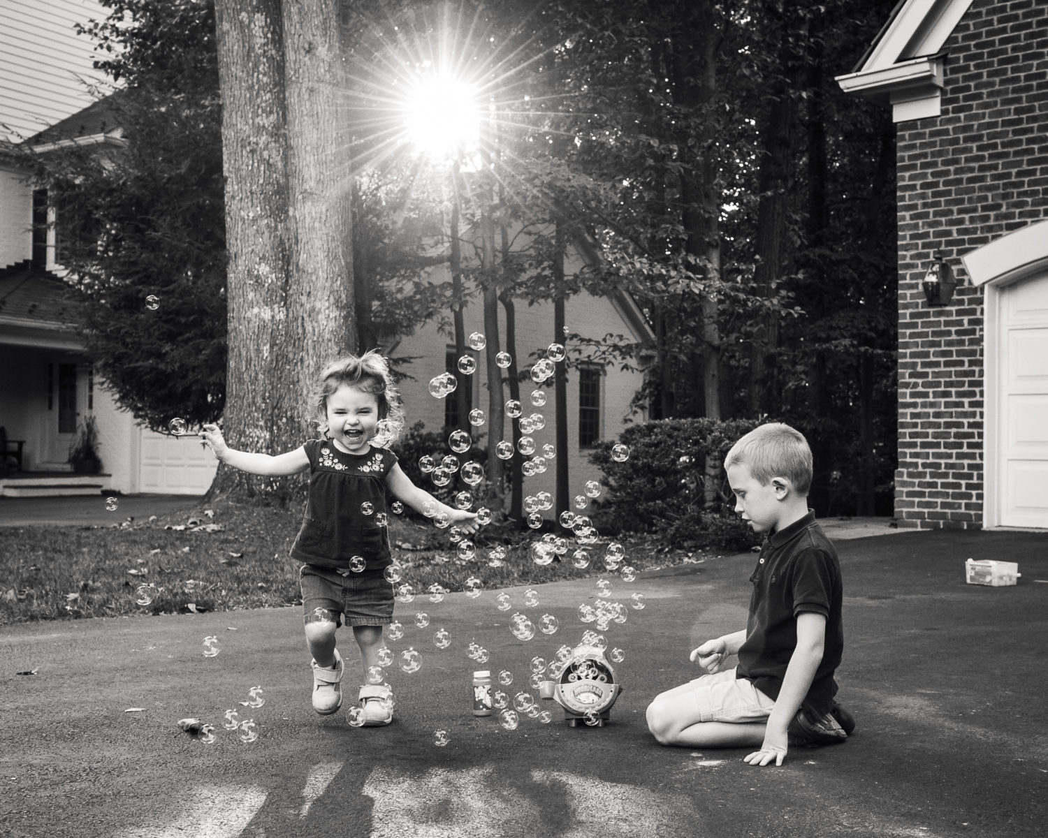toddler laughing at bubbles while brother watches
