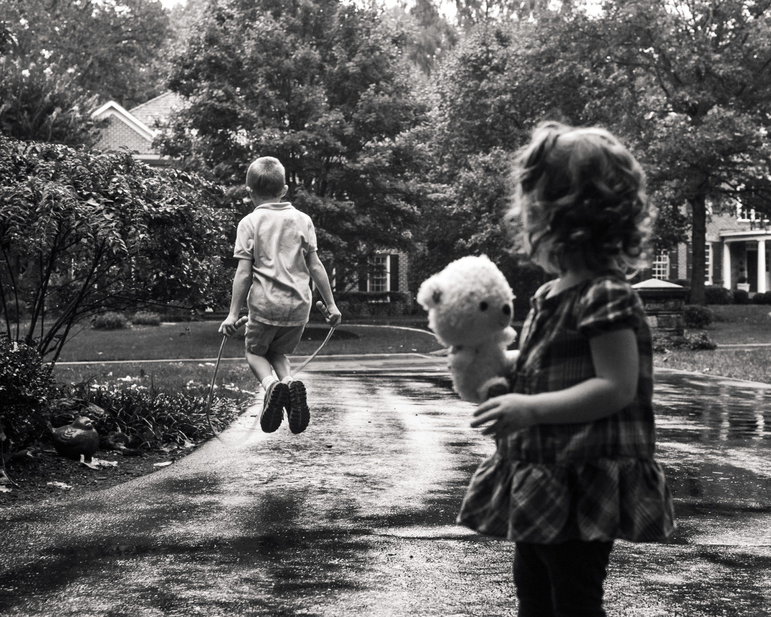Boy jumping rope in the rain while sister watches