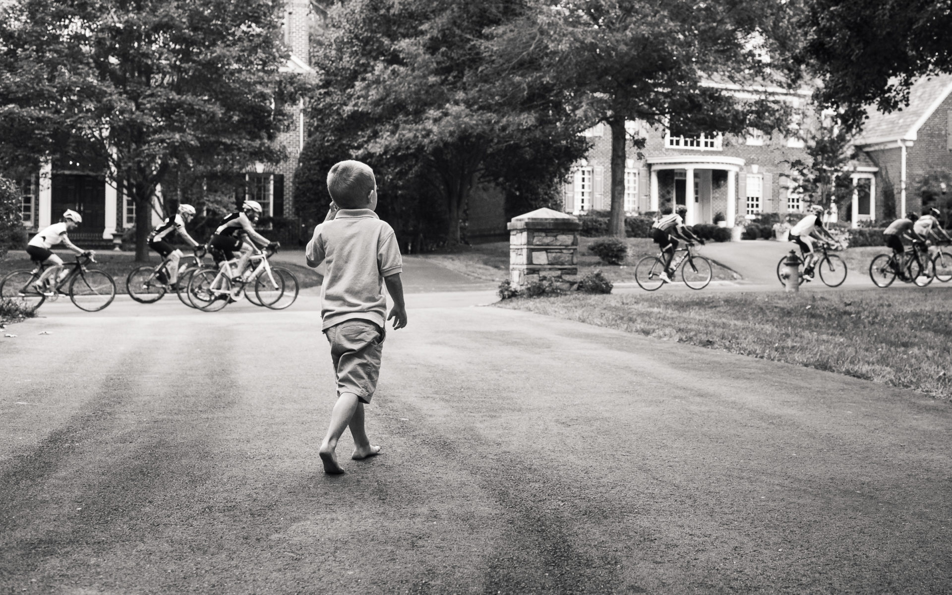 boy watching large troupe of bikers