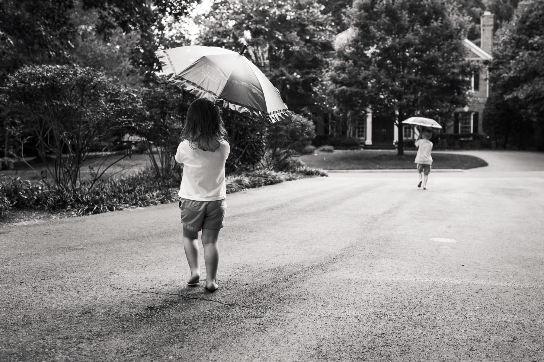 brother and sister playing with umbrellas in the driveway