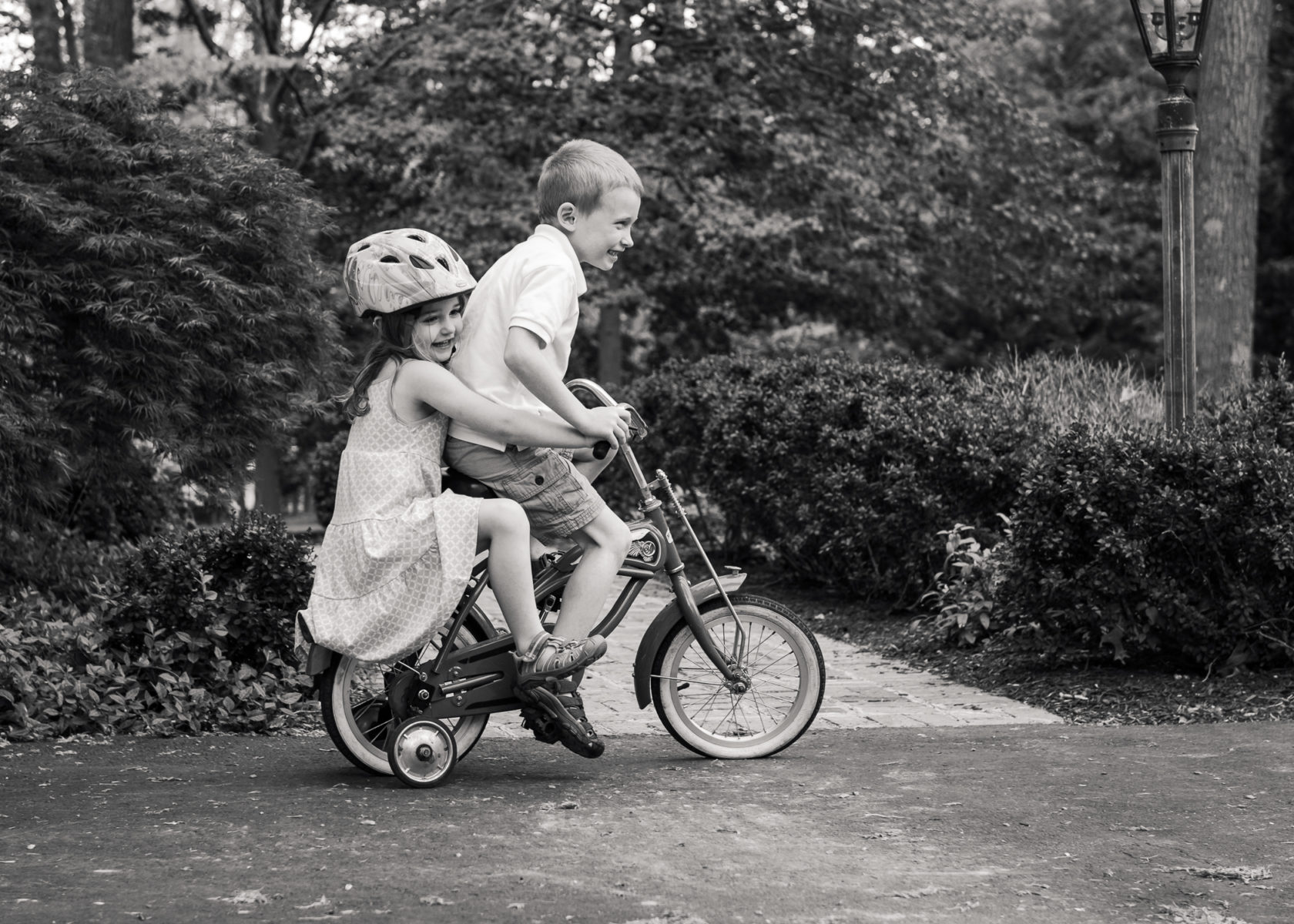 brother and sister sharing too small bicycle