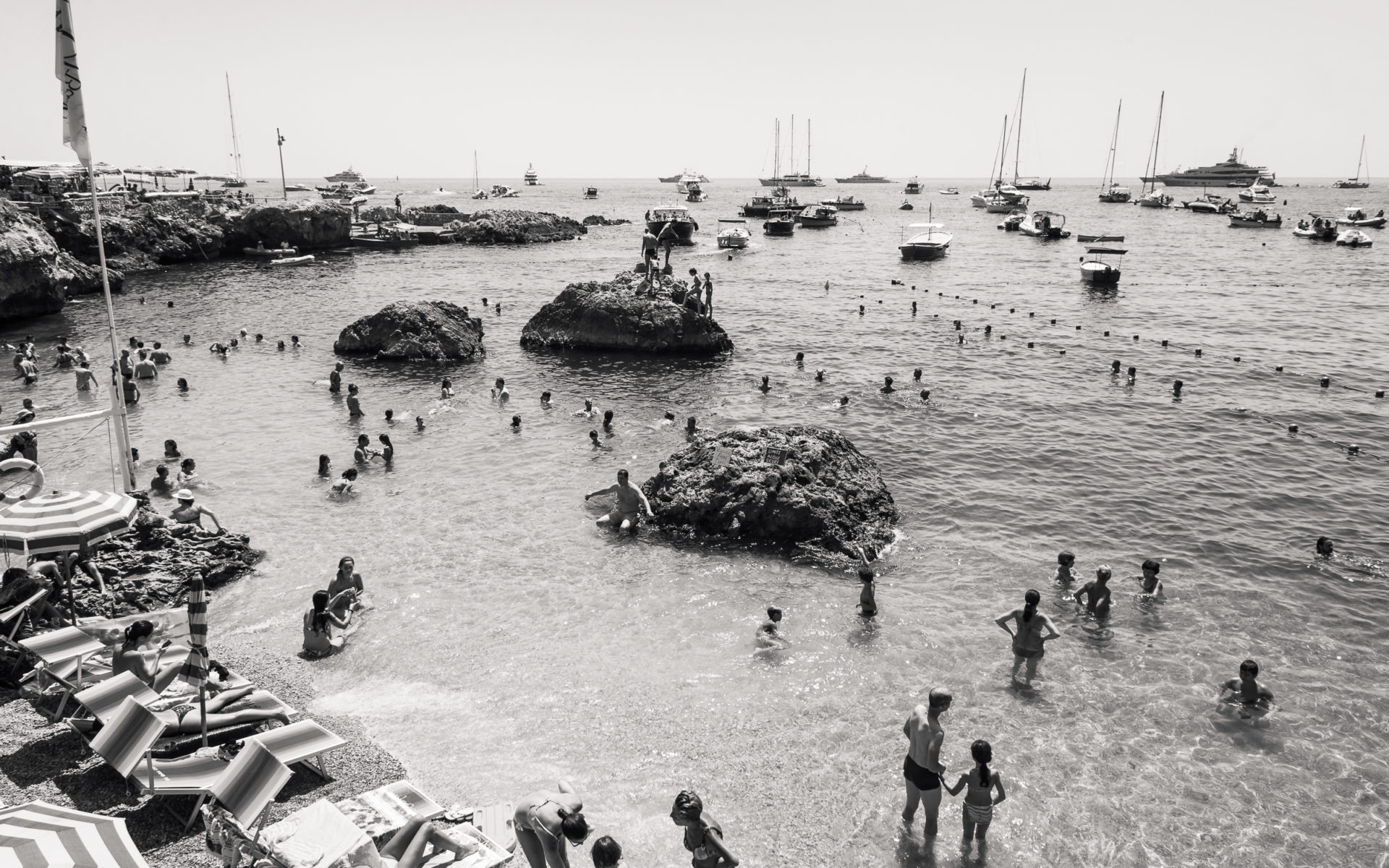 Tourists swimming with boats at Capri Island