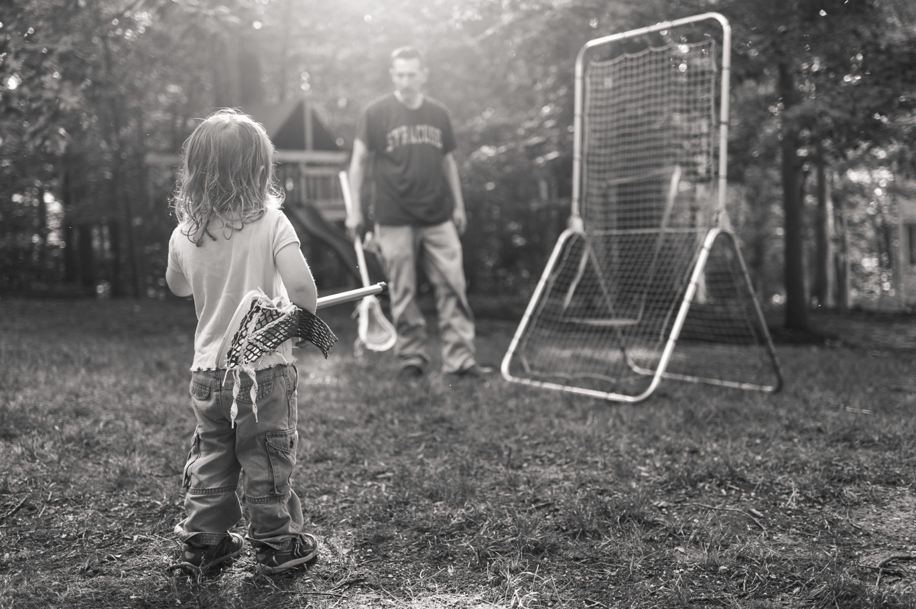 girl waiting to play lacrosse with her dad
