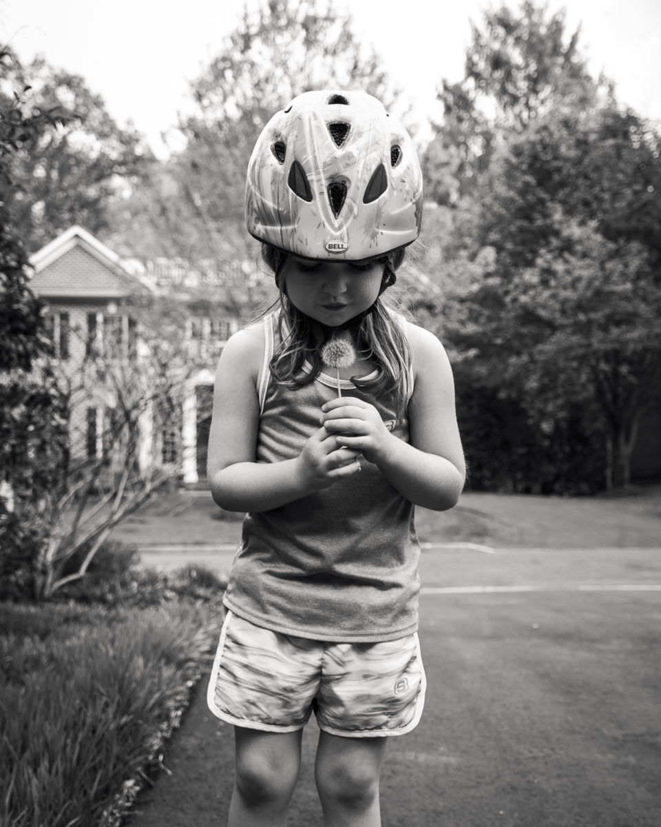 girl holding a dandelion in a bike helmet