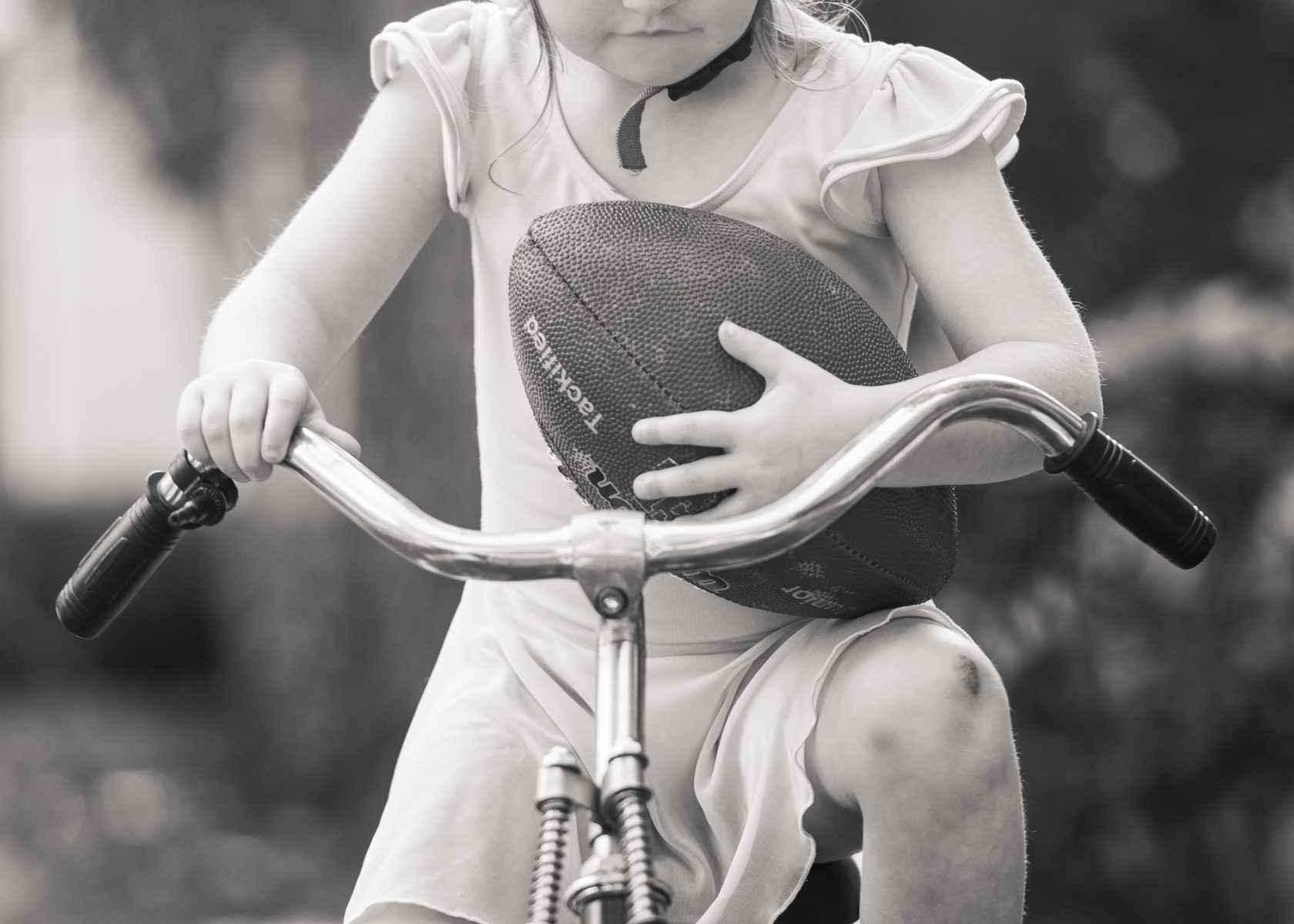 girl wearing leotard riding bike holding football