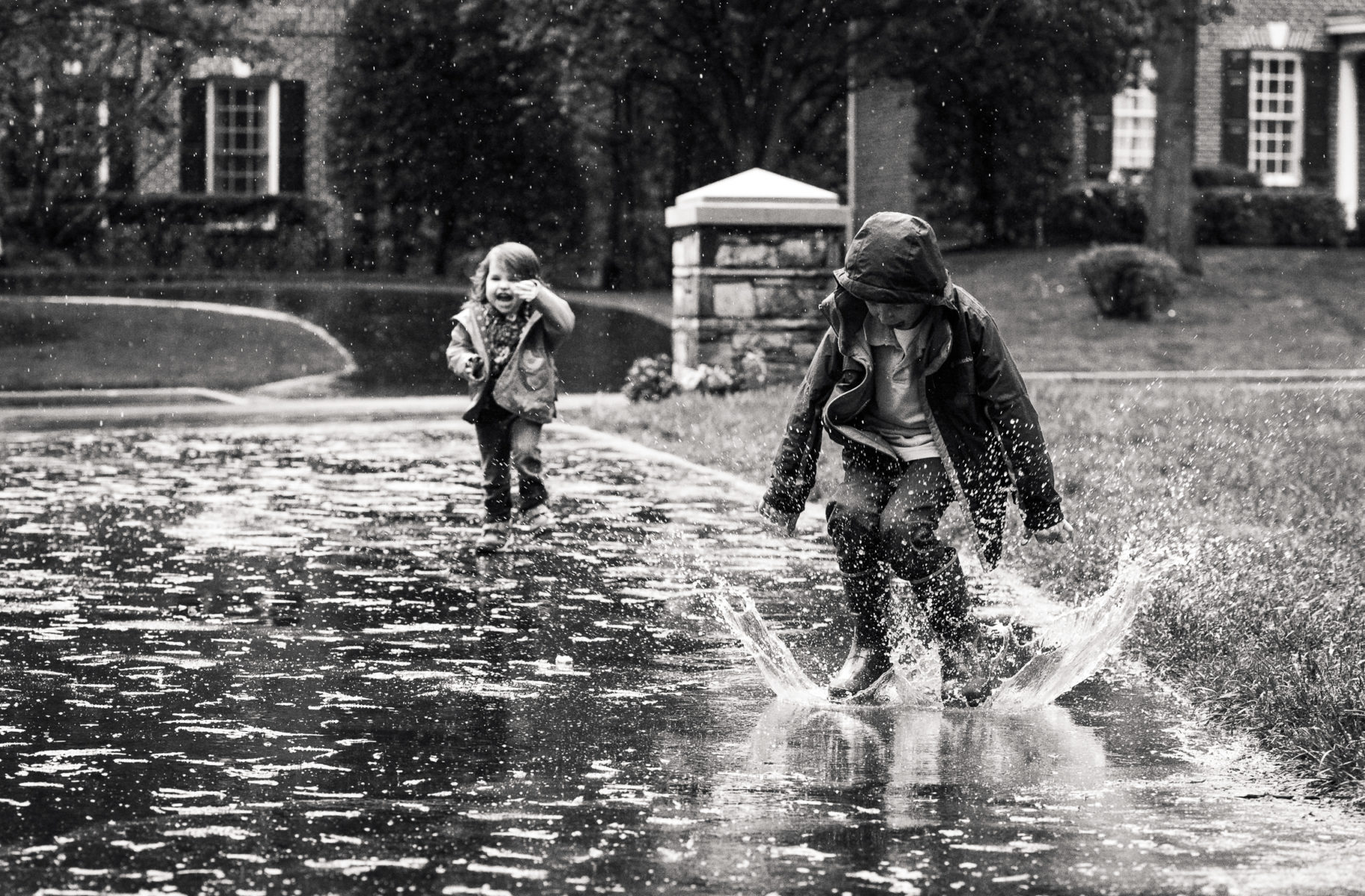 children jumping in puddles on driveway