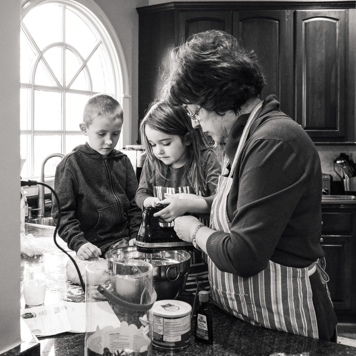 grandmother teaching grandson and granddaughter to cook