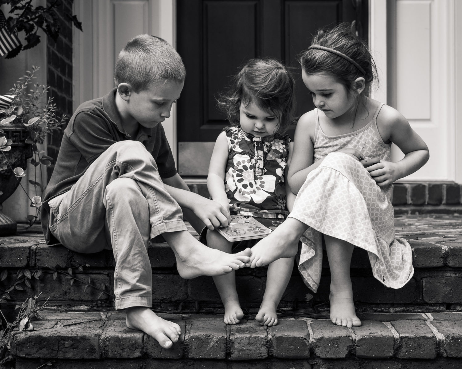 brother and sisters sitting on a front porch together