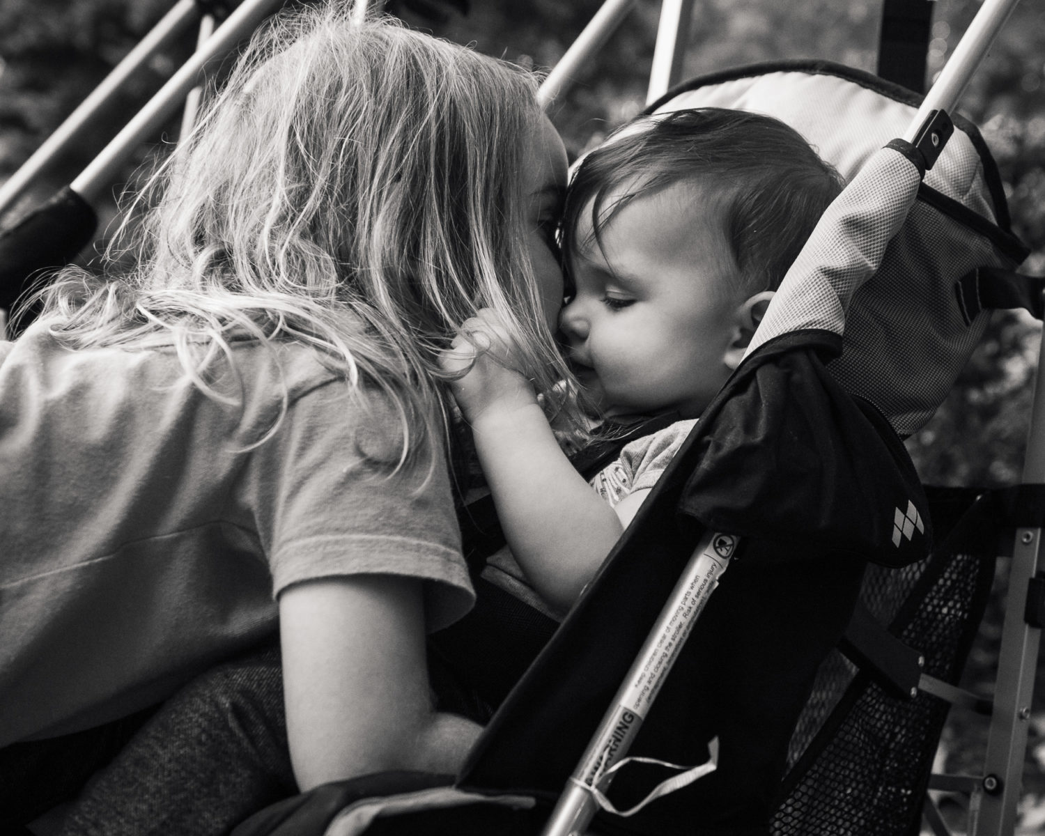 big sister kissing baby in a stroller