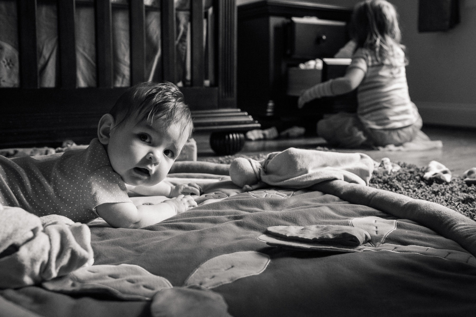baby watching big sister go through her drawers
